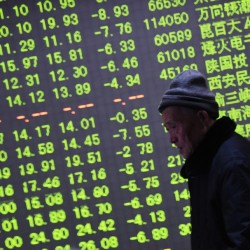 An investor walks past an electronic screen showing stock information at a brokerage house in Hangzhou, Zhejiang province, January 21, 2015. China's stock markets ended sharply lower on Thursday as oil prices gave up the day's rally from 13-year lows and other Asian markets went into reverse. REUTERS/China Daily ATTENTION EDITORS - THIS PICTURE WAS PROVIDED BY A THIRD PARTY. THIS PICTURE IS DISTRIBUTED EXACTLY AS RECEIVED BY REUTERS, AS A SERVICE TO CLIENTS. CHINA OUT. NO COMMERCIAL OR EDITORIAL SALES IN CHINA.